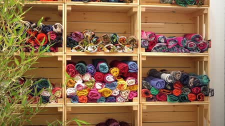 Colorful scarves for sale on a piece of furniture 動画素材