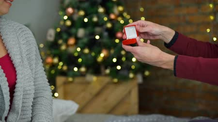 koszorú : Man Giving a Ring near the Christmas Tree Slow Motion