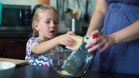 baking dishes : Little Girl Grating Cheese with Mother and Eating It Stock Footage