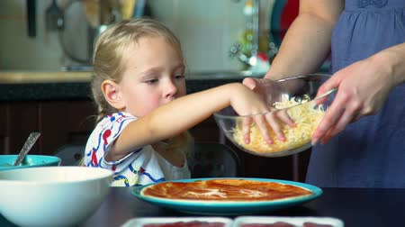 baking dishes : Little Girl Sprinkling Cheese on Pizza Base Stock Footage