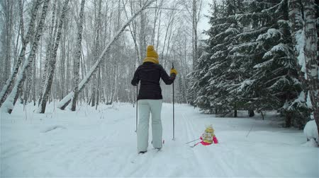 queda de neve : Girl Falls in the Snow While Skiing with Mom