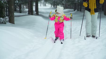 szibéria : Little Girl Learning to Skiing with Mom Stock mozgókép