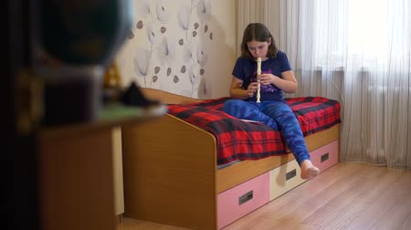 gravador : Girl Playing Flute on Her Bed