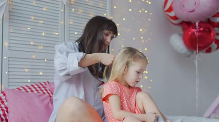 braid hairs : Mother Weaves Braids with Her Daughter on a Bed