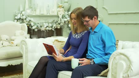 memories photos : Couple Viewing Photos in Christmas living room Stock Footage