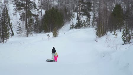 csőrendszer : Mom and Daughter Climbing a Hill with Snow Tube