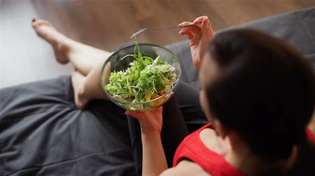 jeść : Young Woman Eating Vegetarian Salad on a Sofa