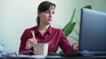 instante : Busy Woman Eating Noodles while Working in Office Stock Footage