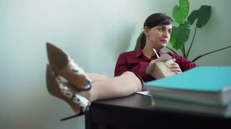 instante : Woman Eating Noodles in office with Legs on Desk