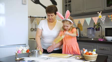 easter : Little Girl Rolling Out a Dough with Grandmother