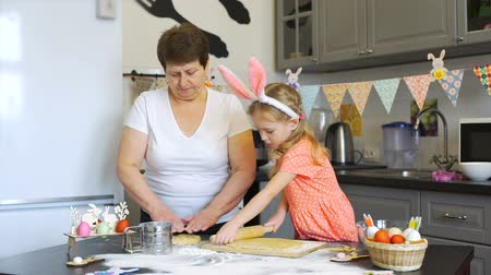 rabbit ears : Little Girl Rolls Out a Dough with Grandmother Stock Footage