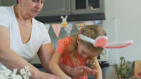 easter : Little Girl with her Gradma Rolling Out a Dough