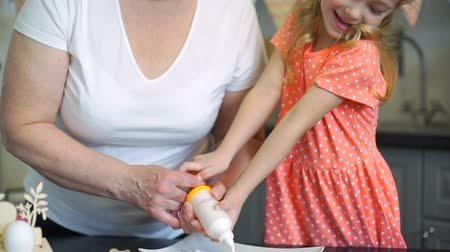 easter : Little Girl Decorating Cookies with Grandmother