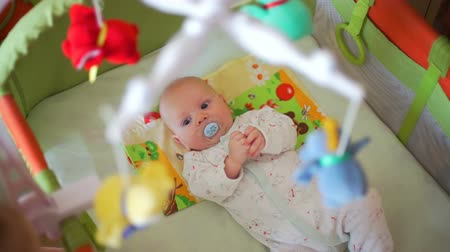 playful infant : Little Baby with Soother Looking at Mobile Stock Footage