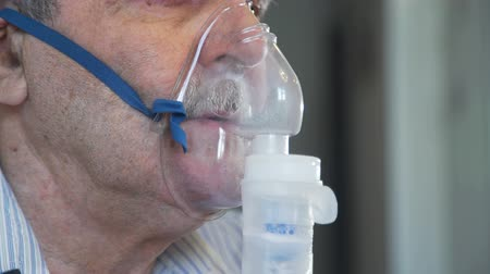 lung : Closeup of an Elderly Man Making Inhalation