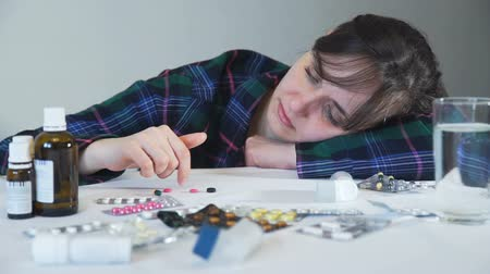antibióticos : Depressed Woman beside a Lot of Pills on a Table