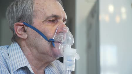 tosse : Elderly Man Making Inhalation with Nebulizer