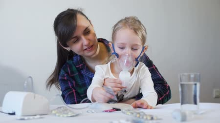 inhalacja : Mother Holding Nebulizer Mask on the Girls Face
