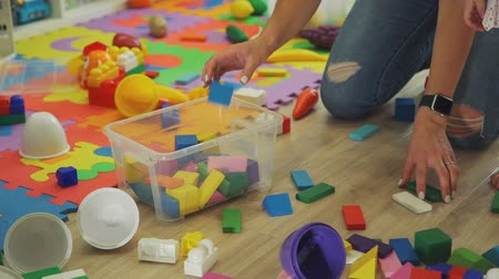 babysitter : Young Woman Clean Up the Nursery from Toys Stock Footage