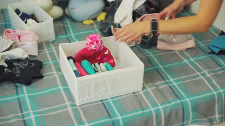 drawer : Woman Putting Baby Clothes into a Box
