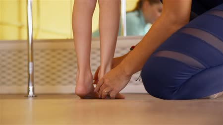 reabilitação : Close-Up of Trainer Physiotherapist Helping Girl Doing Exercises near Barre. Slow Motion. Rehabilitation Restoring after Injury Concept
