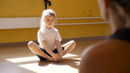 aerobic : Little Girl Doing Stretching Exercises under Trainer Physiotherapist Supervision. Rehabilitation Restoring after Injury Concept Wideo
