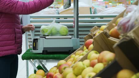 weighing machine : Close-Up of Woman Weighing the Plastic Bag with Apples at a Supermarket Grocery Store. Housewife Shopping in a Supermarket in the Department of Fruit and Vegetables. Sale, Shopping Concept Stock Footage