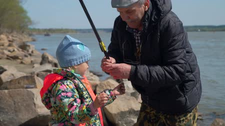 tyč : Elderly Man Giving Freshly Caught Fish to a Young Girl. Grandfather and Granddaughter are Fishing in a Spring Sunny Day. The Concept of Fishing and Leisure Activity in Nature.