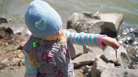 lombrico : Little Girl Holding an Earthworm in her Hands and She is Examining it. She is Going to Fish with her Grandfather. Slow Motion. The Concept of Fishing and Leisure Activity in Nature Filmati Stock