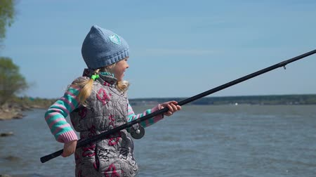 fishing pole : Close-Up Shot of Little Girl Trying to Catch a Fish. She is Standing on a Bank of a River with Large Fishing Pole on Spring Sunny Day. The Concept of Fishing and Leisure Activity in Nature Stock Footage