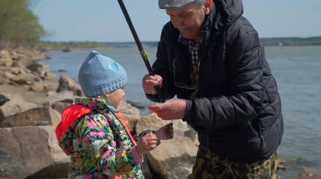životní styl : Senior Man Giving Freshly Caught Fish to his Granddaughter. Grandfather and Granddaughter are Fishing in Spring Sunny Day. The Concept of Fishing and Leisure Activity in Nature. Slow Motion