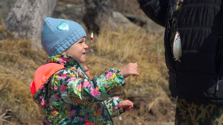 outdoor hobby : Senior Man Showing Freshly Caught Fish to his Grandchild. Young Girl Watching it and Trying to Touch It. The Concept of Fishing and Leisure Activity in Nature Stock Footage