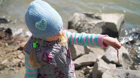 lombrico : Young Girl Holding an Earthworm in her Hands. She is Going to Fish with her Grandfather. The Concept of Fishing and Leisure Activity in Nature