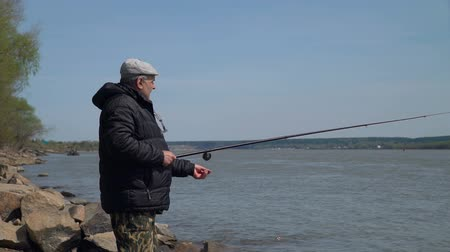 tyč : Senior Man Fishing on a River in a Spring Day. A Fisherman with a Fishing Rod on a River Bank. Spring Fishing Season. The Concept of Quiet Outdoor Recreation. Slow Motion Dostupné videozáznamy