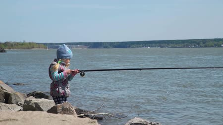 fishing pole : Young Girl Standing on a Bank of a River with Large Fishing Pole on a Spring Sunny Day. Young Girl Fishing on a Bank of River. The Concept of Fishing and Leisure Activity in Nature