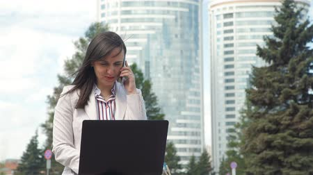 galuska : Businesswoman Talking on Phone while Using Laptop. Young Woman Wearing Business Suit Working Outdoors. Slow Motion. Lifestyle and Business Concept