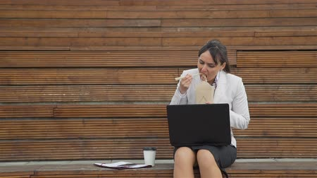 wok food : Businesswoman Eating Junk Food while Using a Laptop in Slow Motion. She is Working Outdoors during Lunch Break. Lifestyle and Business Concept