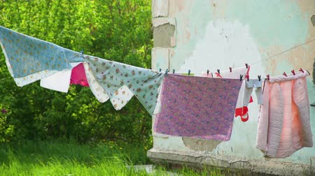 ruhacsipesz : Clothes Hanging on the Clothesline Outdoor Near Run Down House. Wash clothes on a rope with clothespins. Housework and Housekeeping Concept