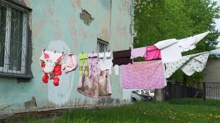 prendedor de roupa : Clothes Hanging on a Clothesline in the Yard in a Disadvantaged Area. Lots of Baby Laundry in the Breeze on a Rope with Clothespins