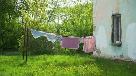ruhacsipesz : Clothes Hanging and Dressed to Dry Outdoors on the Clothesline in Spring Time. Rope with Clean Clothes on Laundry Day. Housework and Housekeeping Concept Stock mozgókép