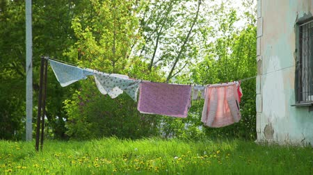 ruhacsipesz : Wash Clothes on a Rope with Clothespins Hanging on the Clothesline Outdoor Near an Old House in Disrepair. Housework and Housekeeping Concept