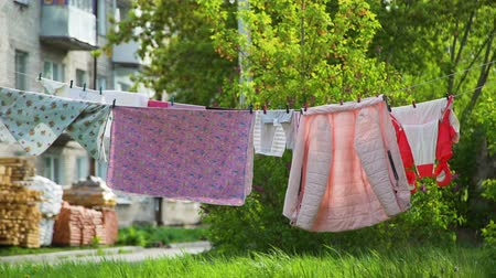 szárítókötél : Rope with Clean Clothes Outdoors on Laundry Day in Spring Time. Clothes Hanging on a Clothesline in the Yard. Housework and Housekeeping Concept Stock mozgókép