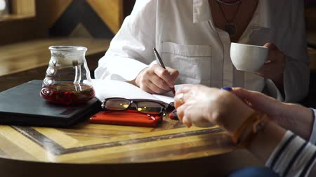 traumatic : Psychologist Taking Notes during Patient Talking in a Coffee House. Close Up View. Psychiatrist Listening to Her Patient Who Experienced Traumatic Events Stock Footage