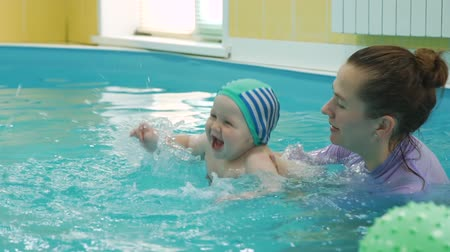instrutor : Cute Baby Enjoying Swimming in a Pool with Swimming Instructor. Early Development Class for Infants Teaching Children to Swim and Dive. Healthy Lifestyle