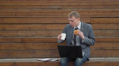 лапша : Handsome Businessman Having a Lunch Break Outdoor. He is Eating a Burger and Drinking Coffee while Using Laptop. Lifestyle and Business Concept