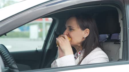 distraído : Businesswoman Eating a a Burger while Sittting in her Car and Talking on Phone during Lunch Break. Slow Motion. Lifestyle and Business Concept Vídeos