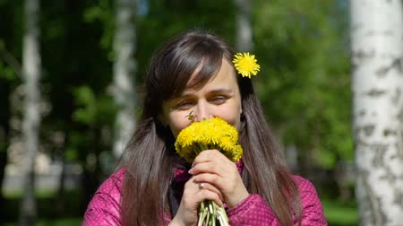 cheirando : Beautiful Caucasian Woman Smelling the Smell of Yellow Dandelions. Smiling Young Beautiful Woman Sniffing Yellow Dandelions in a City Park. Slow Motion.