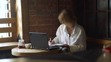 diary : Mature Business Woman Making notes in a Diary in a Cafe. Female Freelancer Working in a Coffee Shop. Online Work and Freelance Concept