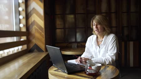 remotely : Business Woman Making Video Call in Coffee Shop in Slow Motion. Mature Woman Working Remotely with her Laptop. Freelance Work, Business People Concept Stock Footage