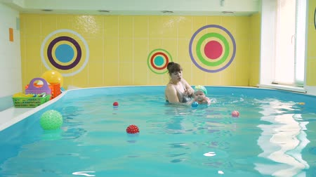 ativo : Infant Baby Girl Enjoying her First Swim in the Pool. Swimming Instructor Teaching a Young Child to Swim in the Pool Holding it in her Arms. Healthy Lifestyle and Early Development Concept